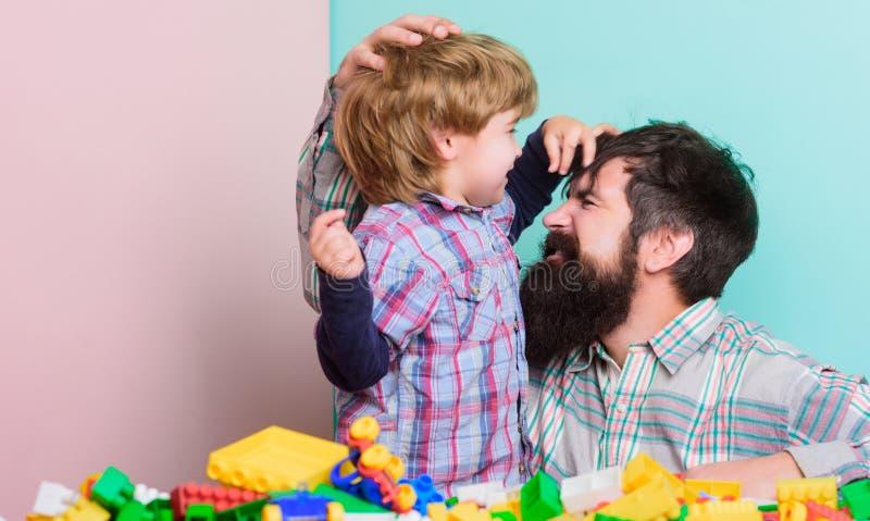 Barnav?rdbegrepp lycklig familj Fadern och sonen har gyckel med tegelstenar Barns utveckling och uppfostran Sk?ggig Hipster royaltyfria foton