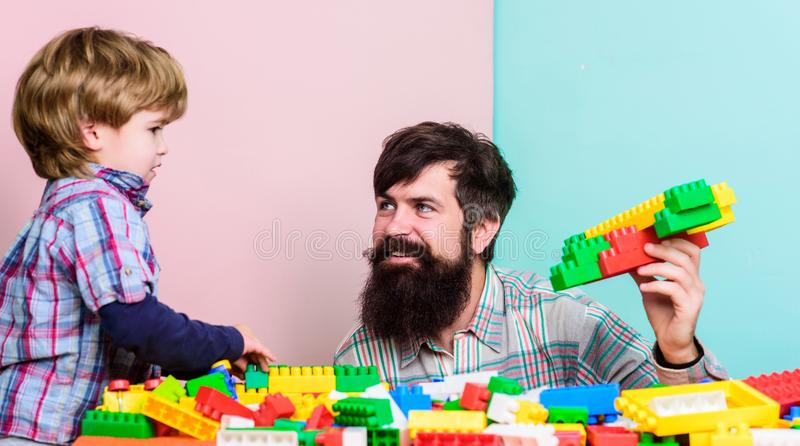 Barnav?rdutveckling Familjfritid Fadersonlek Fadern och sonen skapar konstruktioner Sk?ggig man- och sonlek royaltyfria bilder