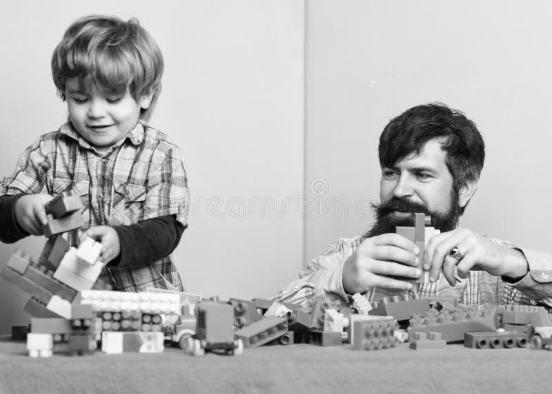 Barnav?rdutveckling och uppfostran Fadersonlek Fadern och sonen skapar f?rgrika konstruktioner med tegelstenar arkivfoto