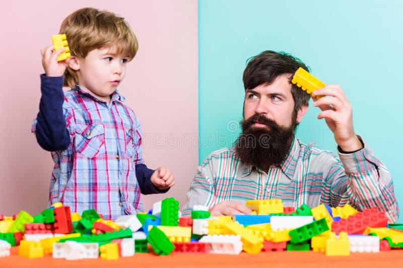 Barnav?rdutveckling och uppfostran Fadersonlek Fadern och sonen skapar konstruktioner Skäggig man- och sonlek arkivbild