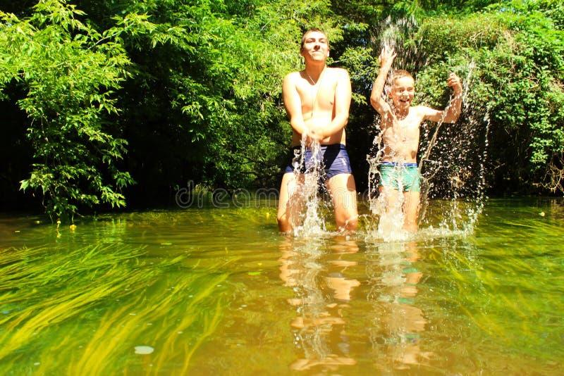 Barnbad Bröder har gyckel i vattnet royaltyfria bilder