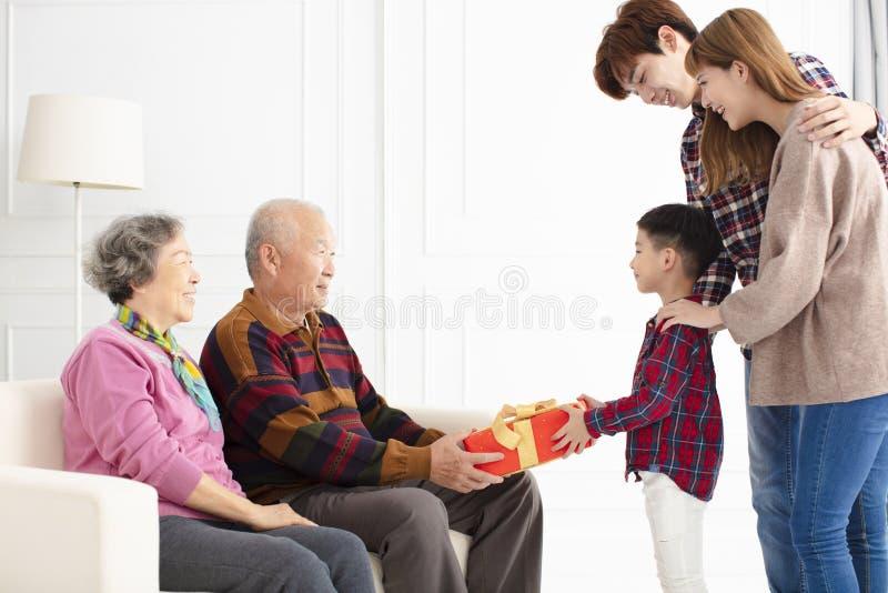 Barnbarn med föräldrar som ger en gåva till morföräldrar arkivbild
