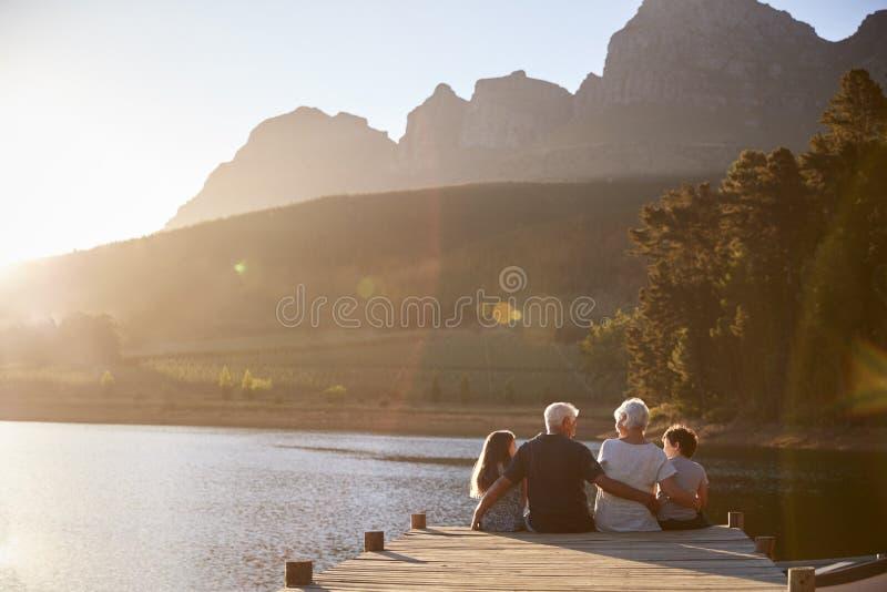 Barnbarn med morföräldrar som sitter på träbryggan vid sjön arkivfoton
