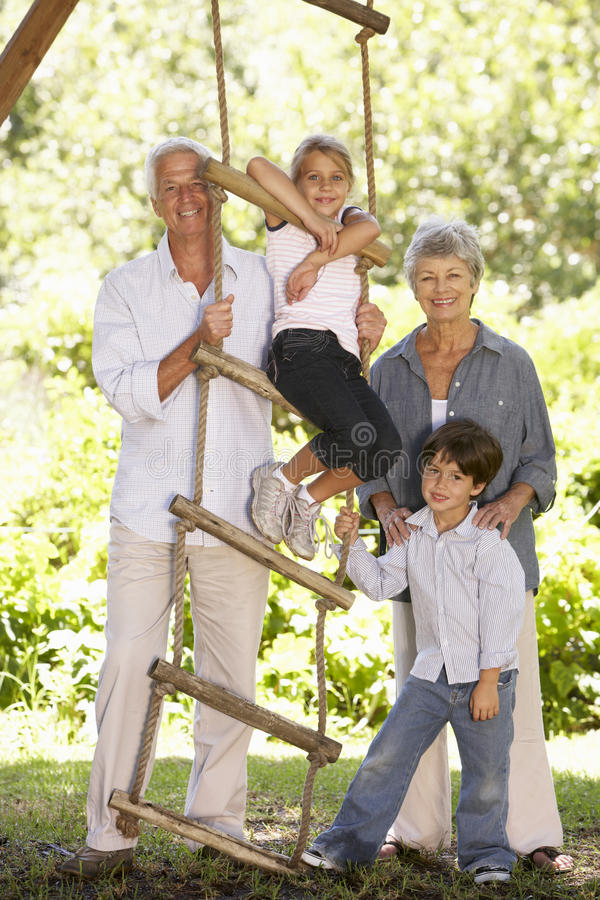 Barnbarn och morföräldrar som står vid trädhuset i trädgård royaltyfri fotografi