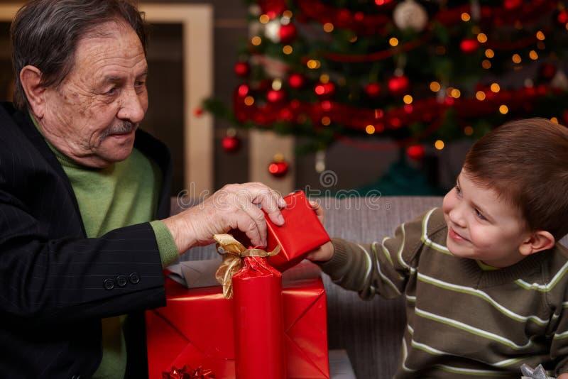 Barnbarn som ger aktuell jul till farfadern arkivfoto
