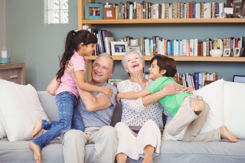 Barnbarn som spelar med morföräldrar royaltyfri fotografi