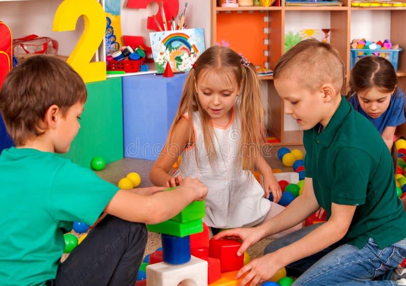 Barnbyggnadskvarter i dagis Gruppungar som spelar leksakgolvet royaltyfri foto