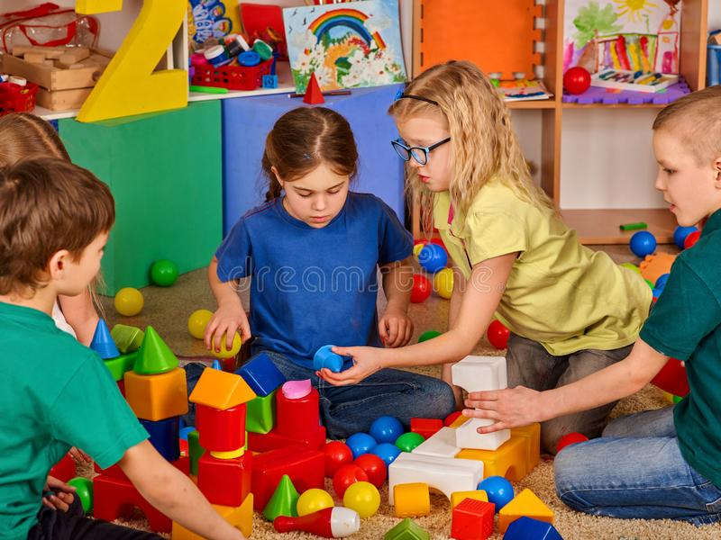 Barnbyggnadskvarter i dagis Gruppungar som spelar leksakgolvet royaltyfri bild