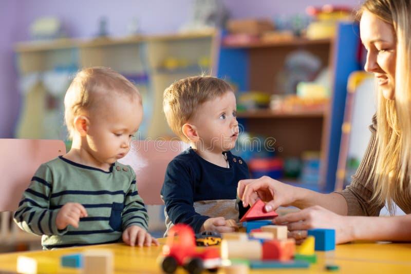 Barnbyggnadskvarter med en lärare i barnkammaren royaltyfria foton