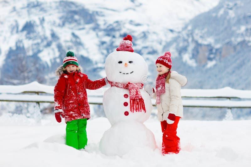 Barnbyggnadssnögubbe Ungar bygger snömannen royaltyfri bild
