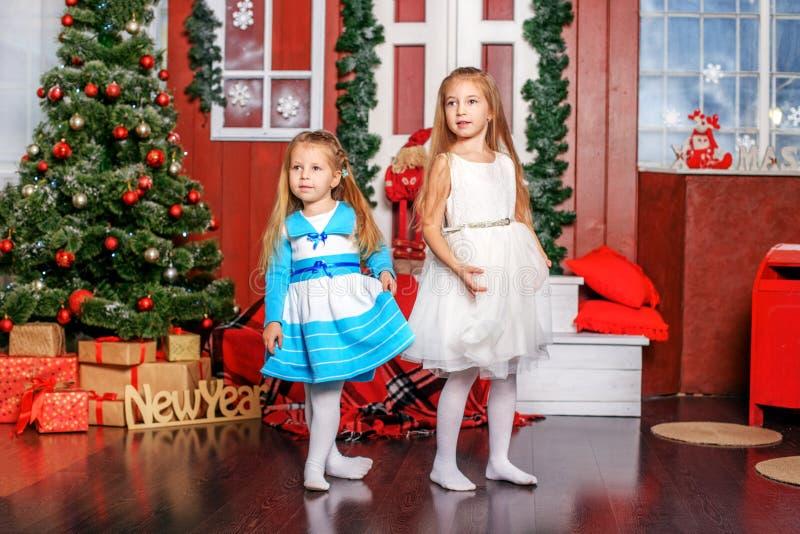 Barndans nära julgranen Nytt år för begrepp som är glat arkivbild