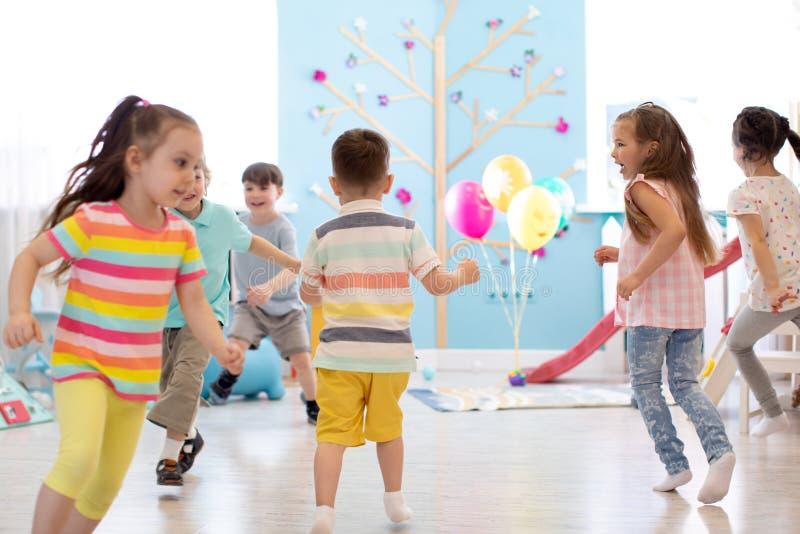 Barndom, fritid och folkbegrepp - grupp av lyckliga ungar som spelar etikettsleken och spring i rymligt rum royaltyfria bilder