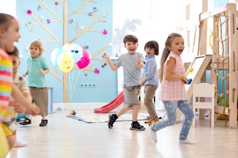 Barndom, fritid och folkbegrepp - grupp av lyckliga ungar som spelar etikettsleken och spring i rymligt rum arkivfoton