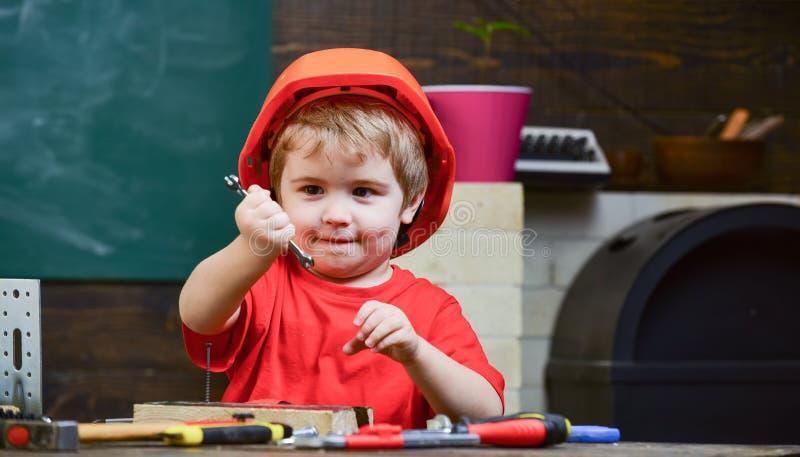 Barndombegrepp Barn som drömmer om den framtida karriären, i arkitektur eller byggande Lura pojken i orange hård hatt eller hjälm royaltyfri bild