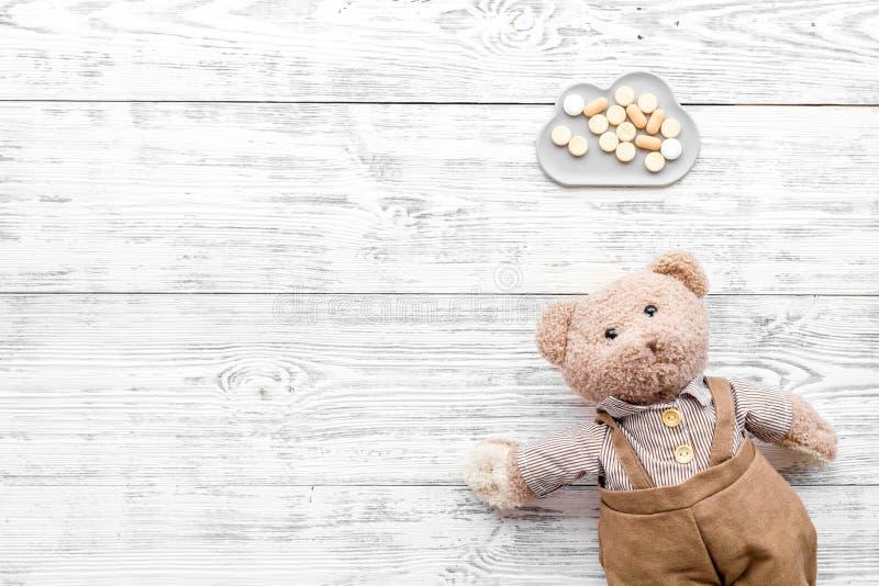 Barndomsjukdombegrepp Behandling av barn Leksak och piller för nallebjörn på den vita träkopian för bästa sikt för bakgrund fotografering för bildbyråer