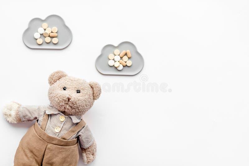 Barndomsjukdombegrepp Behandling av barn Leksak och piller för nallebjörn på vitt utrymme för kopia för bästa sikt för bakgrund arkivbilder