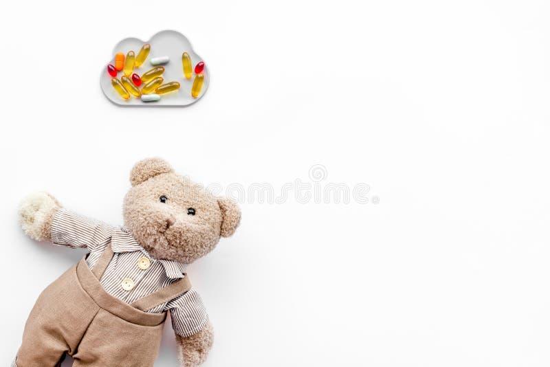 Barndomsjukdombegrepp Behandling av barn Leksak och piller för nallebjörn på vitt utrymme för kopia för bästa sikt för bakgrund arkivfoto