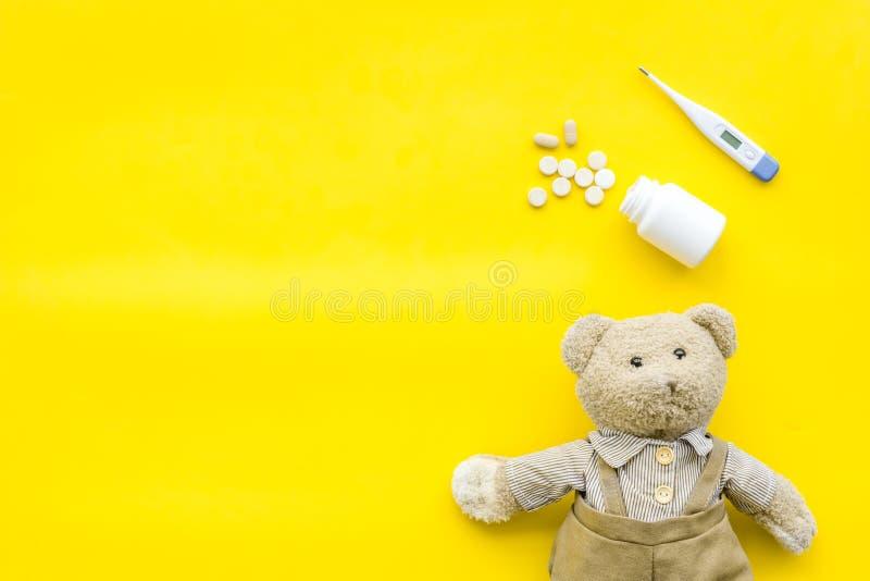 Barndomsjukdombegrepp Behandling av barn Leksak, termometer och piller för nallebjörn på bästa sikt för gul bakgrund royaltyfria bilder