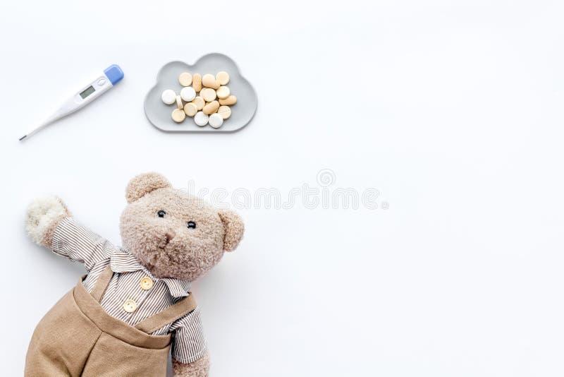 Barndomsjukdombegrepp Behandling av barn Leksak, termometer och piller för nallebjörn på bästa sikt för vit bakgrund arkivfoto