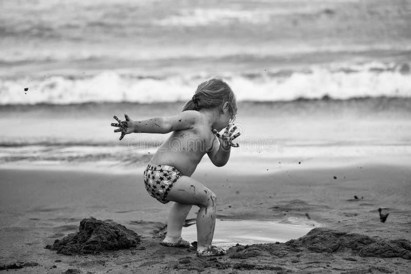 Barnet är på en havsferie Gulligt lerigt behandla som ett barn pojkelekar med våt sand fotografering för bildbyråer