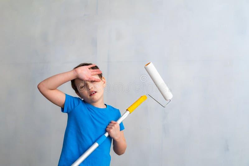 Barnet är trött av att måla väggarna avslutande arbete i lokalen av konstnären målar väggarna reparation av lokal, arkivfoto