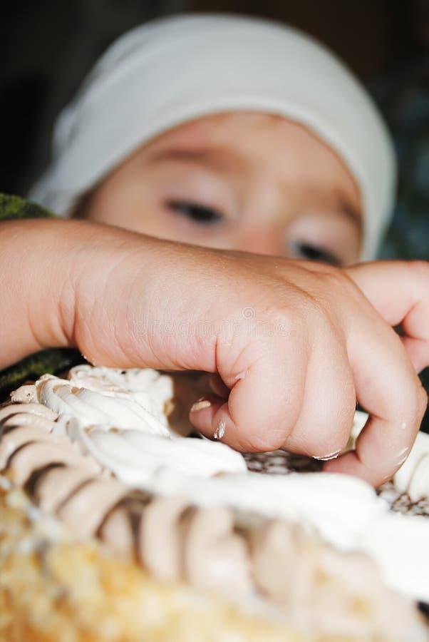 Barnet äter med handkakan royaltyfri fotografi