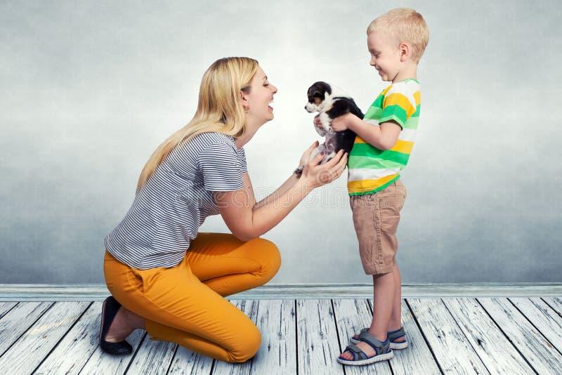 Barnet att framlägga hans moder en liten valp arkivbild