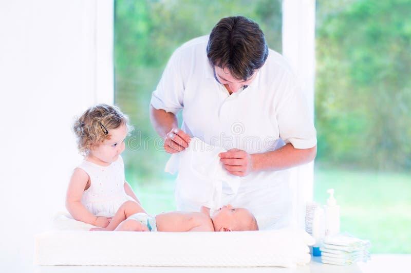 Barnet avlar att klä hans nyfödda son och daugher arkivfoto