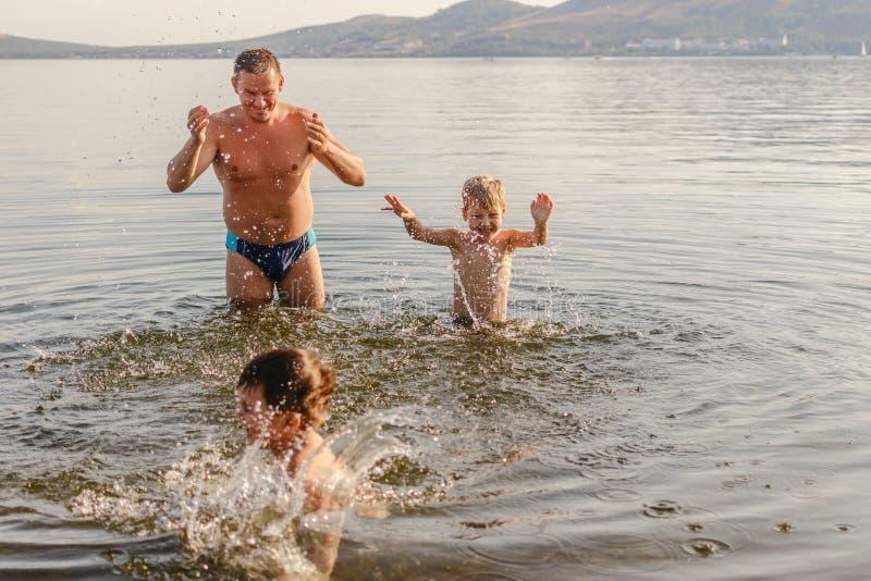 Barnet avlar att spela med två barn i sjön i sommar arkivfoto