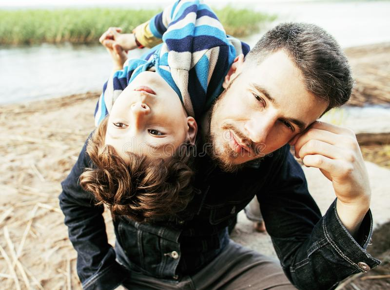 Barnet avlar hipsteren med ett skägg och hans lilla son på sjön arkivbild