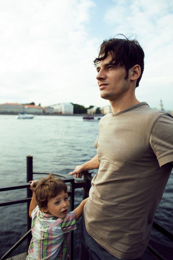 Barnet avlar hipsteren och hans lilla son på flodkusten Tal royaltyfri foto