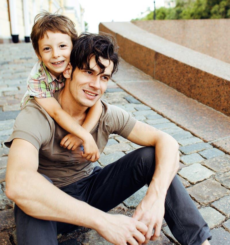 Barnet avlar hipsteren och hans lilla son utanför Tala och att undervisa och att krama och att ha rolig lycklig tid livsstilfolk royaltyfri fotografi