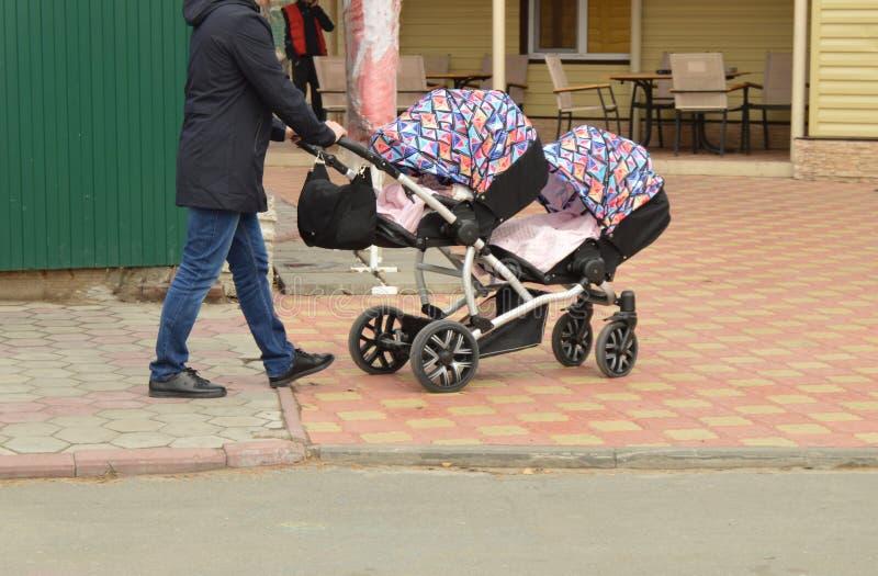 Barnet avlar med en sittvagn för kopplar samman går i parkera på våren royaltyfri foto