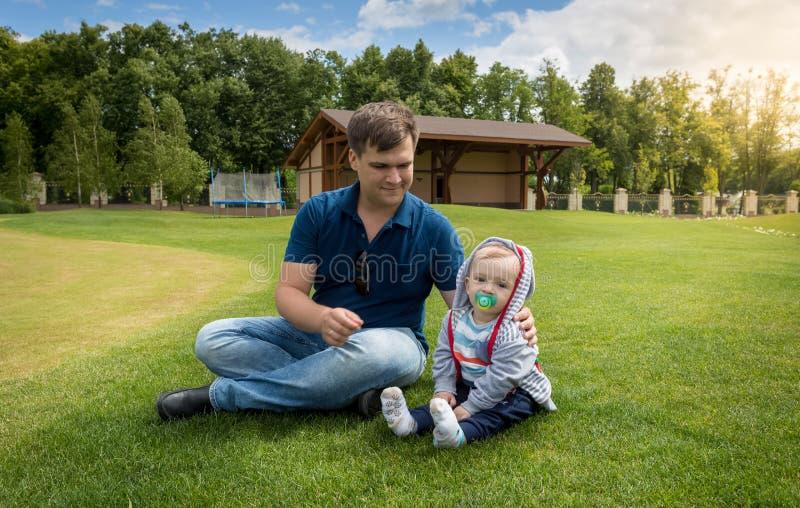 Barnet avlar med hans behandla som ett barn sonen som kopplar av på gräs på, parkerar på sunn arkivfoto