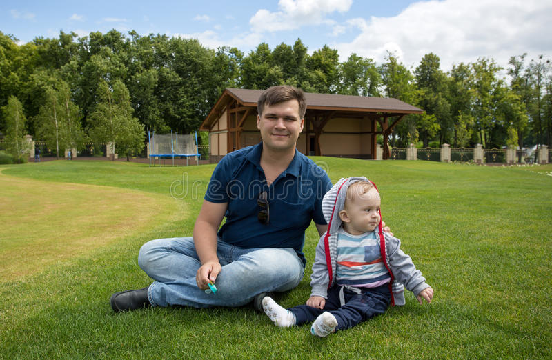 Barnet avlar med hans 9 gamla månader behandla som ett barn pojken som kopplar av på gräs på royaltyfri fotografi