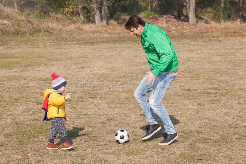Barnet avlar med hans lilla son som spelar fotboll, fotboll i parkera royaltyfri foto