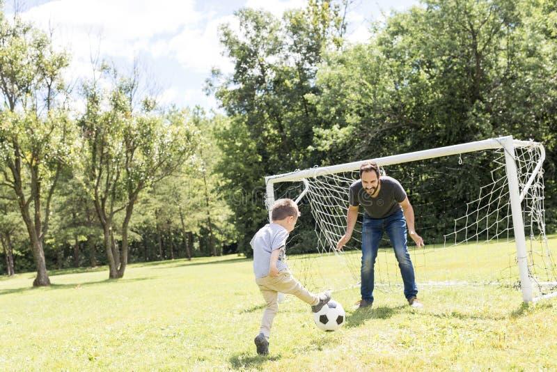Barnet avlar med hans lilla son som spelar fotboll på fotbollgraden royaltyfri fotografi