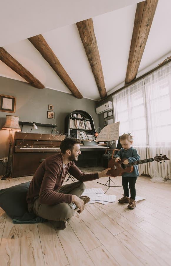 Barnet avlar och den lilla dottern som spelar den akustiska gitarren fotografering för bildbyråer