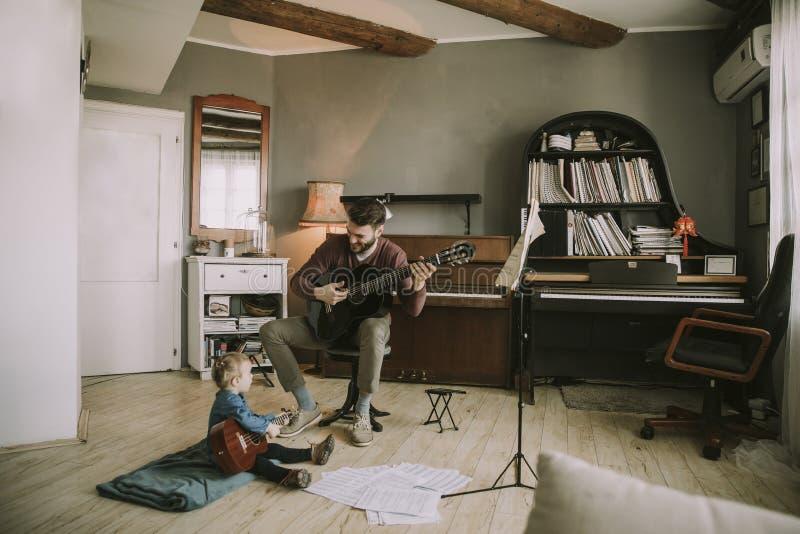 Barnet avlar och den lilla dottern som spelar den akustiska gitarren royaltyfri bild