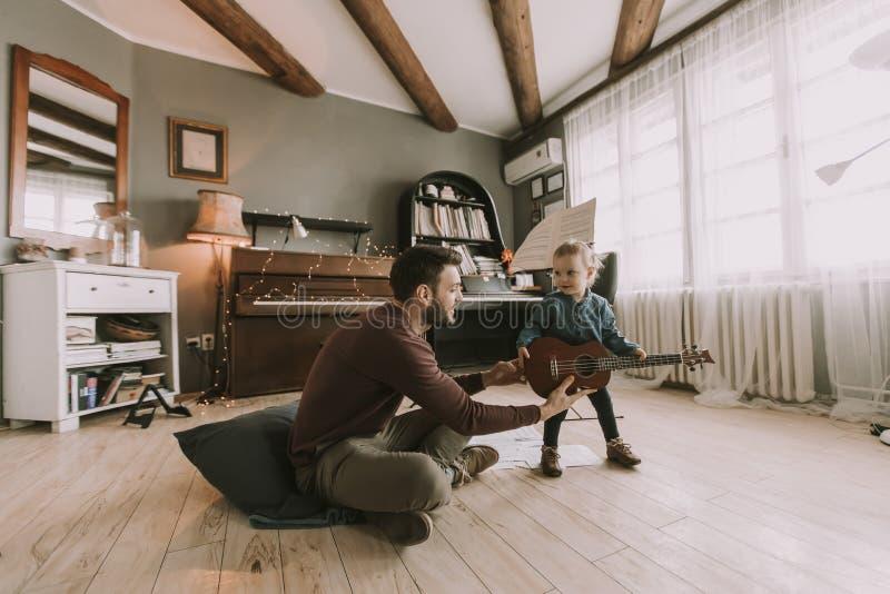 Barnet avlar och den lilla dottern som spelar den akustiska gitarren arkivbild