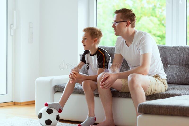 Barnet avlar och hans för världsfotboll för sonen hållande ögonen på mästerskap med arkivbilder