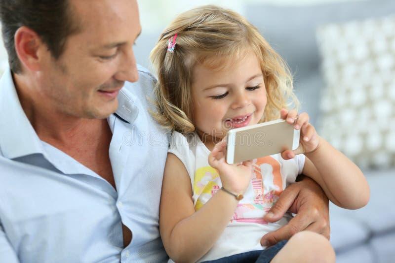 Barnet avlar och hans lilla dotter som tillsammans spelar royaltyfria foton