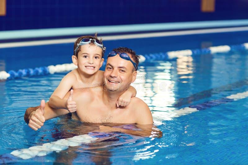 Barnet avlar och hans lilla son i en inomhus simbassäng arkivfoton