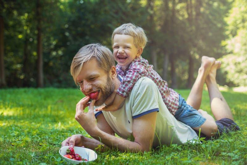 Barnet avlar, och hans son som äter jordgubbar parkerar in picknick utomhus- stående royaltyfri foto