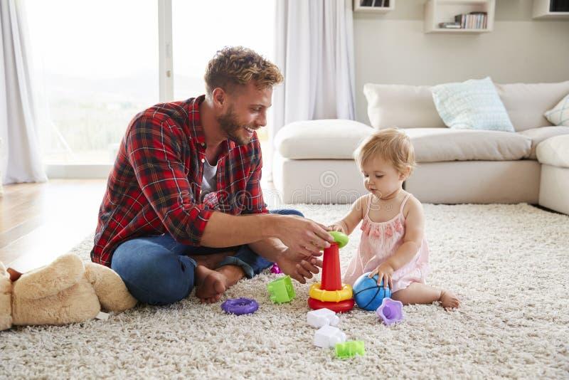 Barnet avlar och litet barndottern som spelar i vardagsrum royaltyfri foto