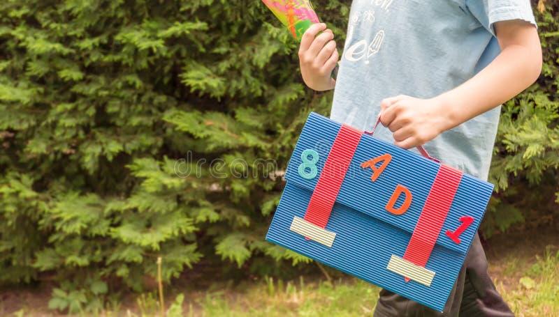 Barnet bär den sockerpåsen och axelväskan till ett skola parti fotografering för bildbyråer