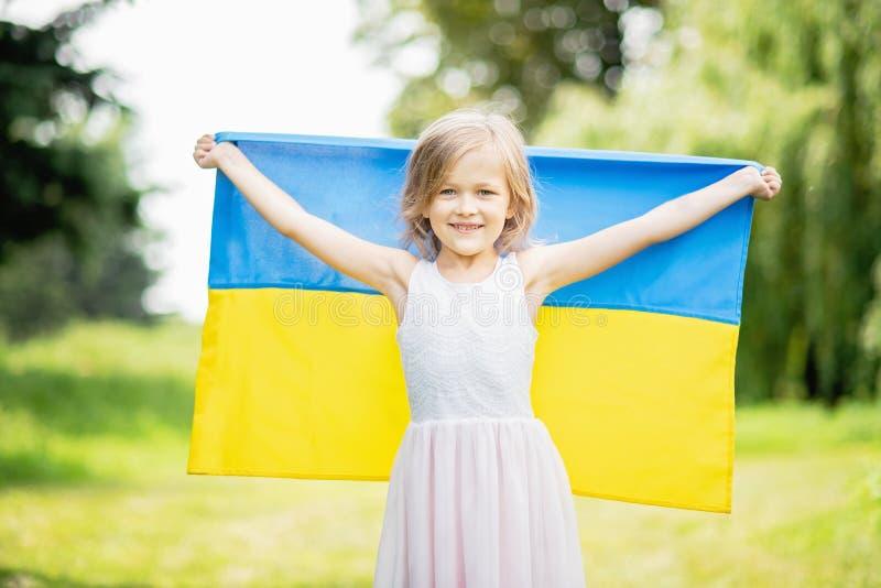 Barnet b?r att fladdra den bl?a och gula flaggan av Ukraina i f?lt Sj?lvst?ndighetsdagen f?r Ukraina ` s f?r dagfyrverkerier f?r  royaltyfri fotografi