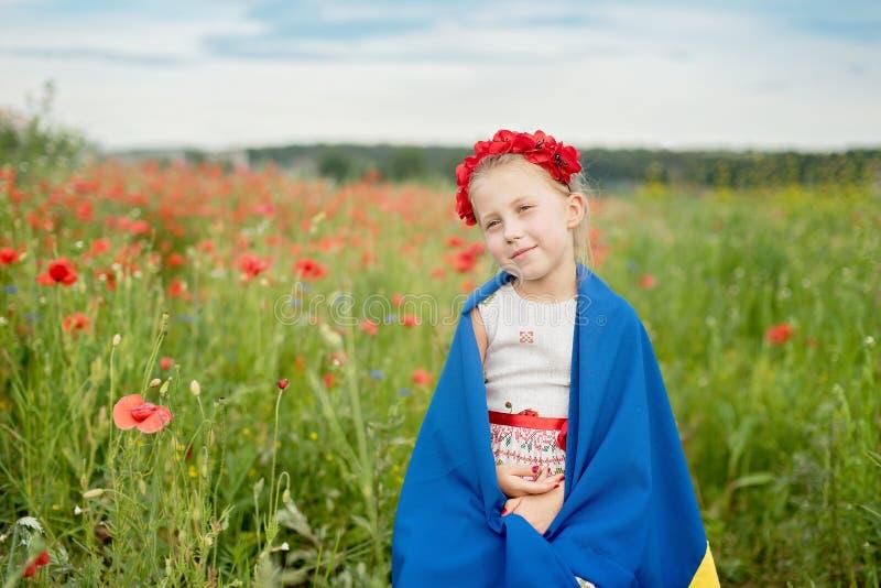 Barnet b?r att fladdra den bl?a och gula flaggan av Ukraina i f?lt Sj?lvst?ndighetsdagen f?r Ukraina ` s f?r dagfyrverkerier f?r  royaltyfri bild