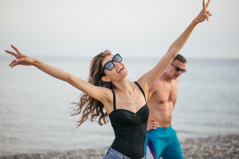Barnet bantar den härliga kvinnan på stranden, skämtsamt som dansar, sommarsemester och att ha gyckel, det positiva lynnet som är royaltyfri bild