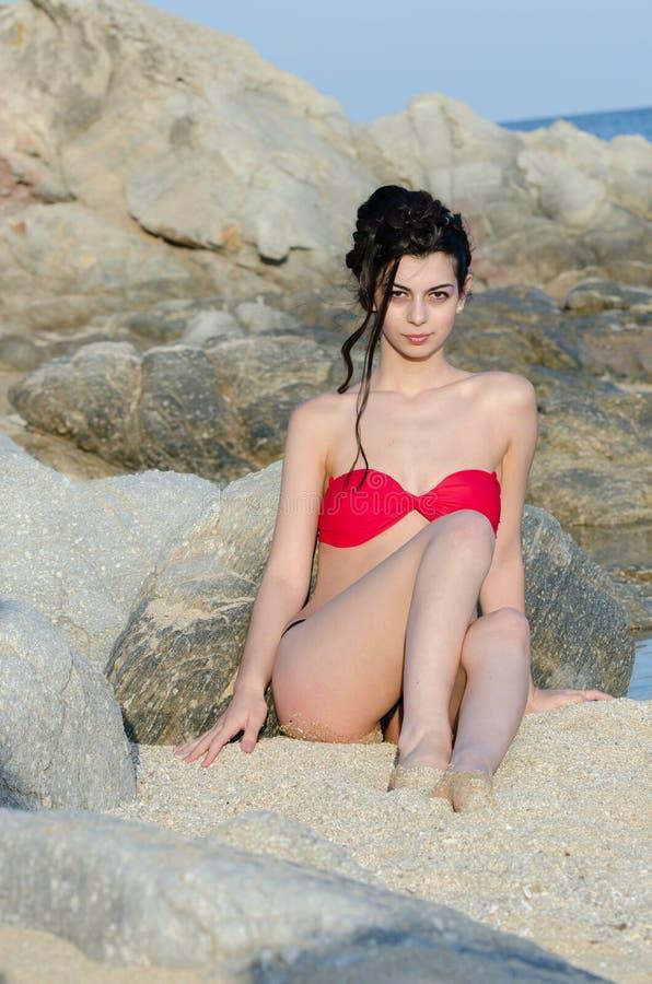 Barnet bantar nätt rött och svart bikinisammanträde för damkläder på sand royaltyfri foto